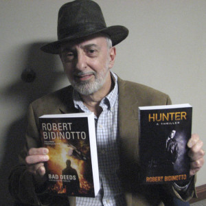 The Vigilante Author poses with his two thrillers (photo by Theresa Winslow, The Capital)